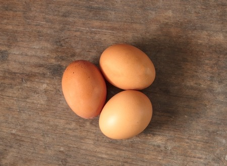 Eggs, Three brown eggs on wooden background. photo