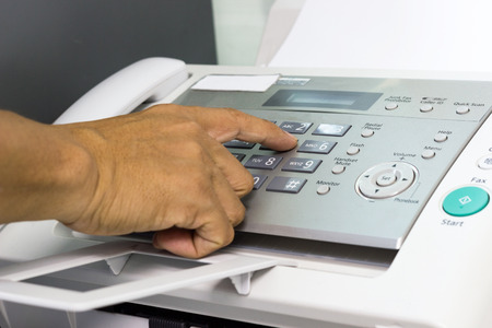 hand man are using a fax machine in the office. Business concept 写真素材
