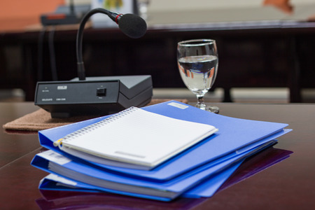 blue files folder retention of contracts, note paper and Glass on brown desk in the conference room