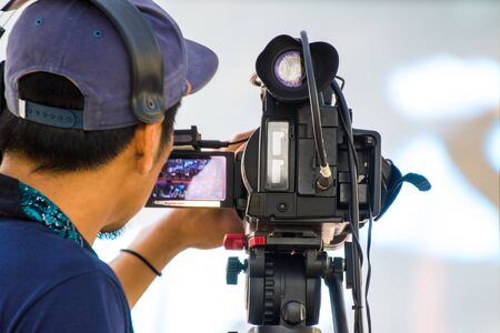 professional cameraman - covering an event to a live and record video at outdoor Archivio Fotografico