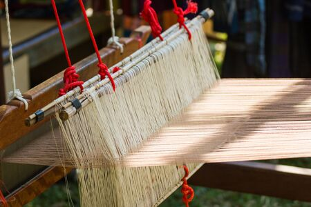 Household Loom weaving - Detail of weaving loom for homemade silk or textile production of Thailand Stock Photo