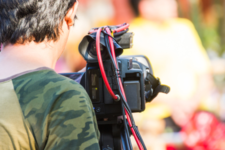 professional cameraman - covering an event to a live and record video at outdoor Stock Photo