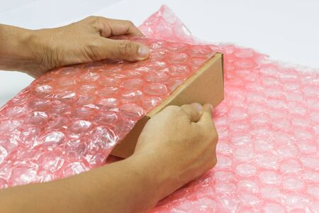 Hand des Mannes halten Blasen, die die Schachtel mit Plastikfolie bedecken, um Schutzprodukt zu knacken oder Versicherung während des Transports - isolierter weißer Hintergrund
