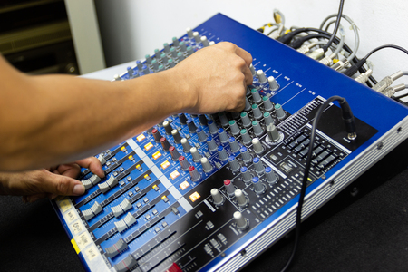 Men hands are controlling the console of a large hi-fi system. Sound equipment. Control panel of a digital studio close-up mixer. Imagens