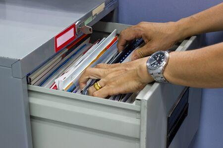 Hand of Man Search files document in a file cabinet in work office, concept business office life. Reklamní fotografie