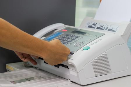 El hombre de la mano está utilizando una máquina de fax en la oficina. Concepto de negocio