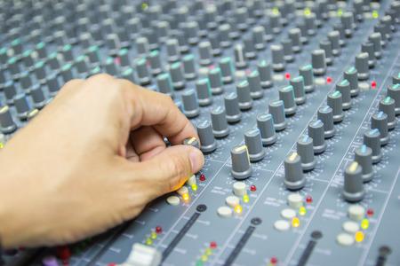 Close-up hand of man control Mixing Console of a big HiFi system The audio equipment, control panel of digital studio mixer. Imagens