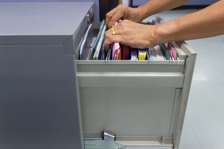 Hand of Man Search files document in a file cabinet in work office, concept office life. Imagens - 111070347