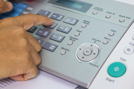 Hand man are using a fax machine in the office, Business concept office life Stock Photo