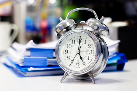 Reloj en la mesa de trabajo en la oficina Tiempo del empresario conceptos de trabajo Foto de archivo