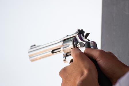 L'uomo tiene una pistola pronta a sparare praticando le riprese nel parco fuoco selettivo sulla parte posteriore della pistola