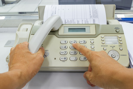 Hand man are using a fax machine send paper in the office Business concept