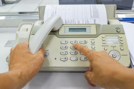 Handmann verwendet ein Faxgerät, das Papier im Büro sendet Geschäftskonzept