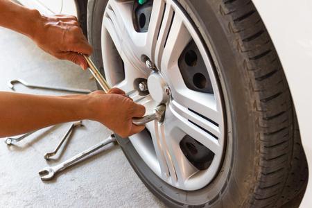 Car mechanician changing tire car wheel in auto repair shop