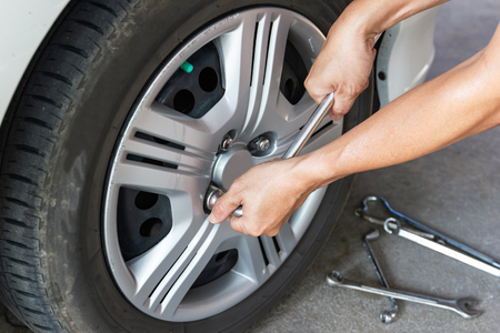 Car mechanician changing tire car wheel in auto repair shop