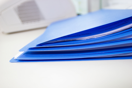 Blue files folder and paper on white table in office, concept Office supplies