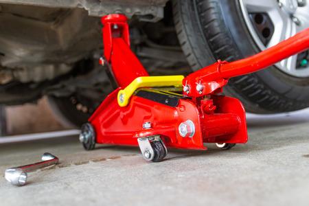 Coche elevador de gato de herramientas rojo para revisión de reparación Mantenimiento de automóviles