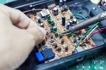 Technician repairing electronic of the computer's circuit board by soldering Irons, concept  technology of computer circuit hardware
