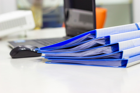 Blue Document folder with documents and Notebook on white table in meeting room