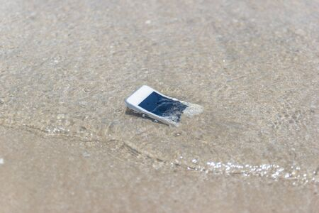 White Mobile phone floated to the sea at the beach. Stok Fotoğraf - 130127697