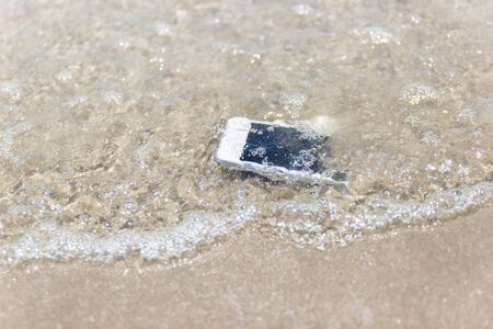 White Mobile phone floated to the sea at the beach.