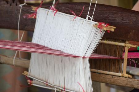 Weaving equipment Household weaving - Detail of weaving loom for homemade silk Used for silk weaving or textile production of Thailand Standard-Bild - 122566091