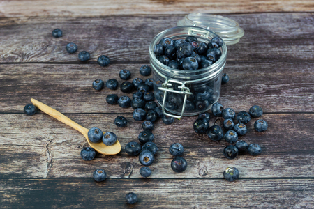 Fresh blueberries in the glass Bottle on wood table