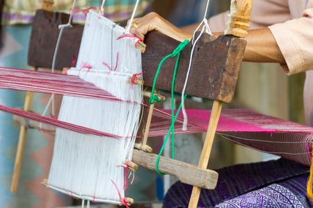Weaving equipment Household weaving - Detail of weaving loom for homemade silk Used for silk weaving or textile production of Thailand Standard-Bild - 124619794