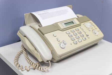 La máquina de fax para enviar documentos en el concepto de equipo de oficina necesario en la oficina