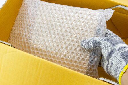 La mano del hombre mantenga el paquete, para el producto de paquete de protección agrietado o seguro durante el tránsito aislado y fondo blanco.