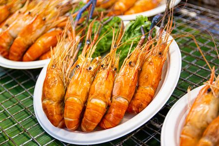 Grilled shrimps of seafood Street food of Thailand on the table in market of Bangkok Thailand Imagens