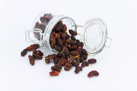 closeup many mulberry in the small Glass jar on white background