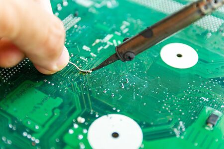 Technicians are using a soldering iron for repairing electronic of the computer circuit board concept technology of computer circuit hardware. Stok Fotoğraf