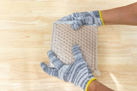 hand of man hold plastic wrap, for protection parcel product cracked or insurance During transitt