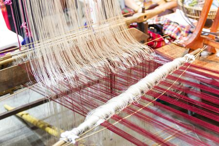 Weaving equipment Household weaving - Detail of weaving loom for homemade silk Used for silk weaving or textile production of Thailand Stock Photo