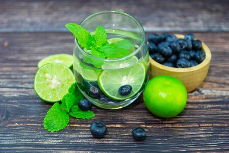 lemon with blueberry in glass on wood table for hot summer days and good for health Banque d'images - 130127733