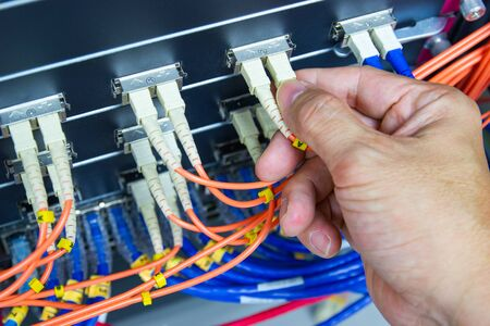 Technician connect fiber cable network to switch port in server room , Concept internet network management