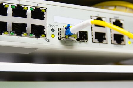 cable network, fiber optic cable connect to switch port in server room, Concept network management Stockfoto
