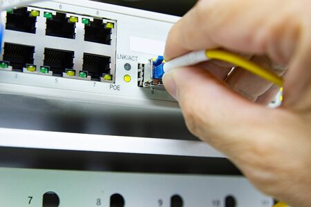 Technician connect fiber cable network to switch port in server room, Concept internet network management Stockfoto