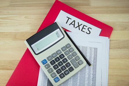 Tax documents and paper files, calculator on the wooden desk in the office,  concept Annual tax payment Imagens