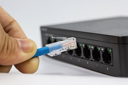 Hand of man holding The network cables to connect Lan port, concept Communication connection technology
