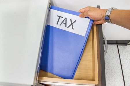 Hand of Man hold Tax Files folder in the file cabinet