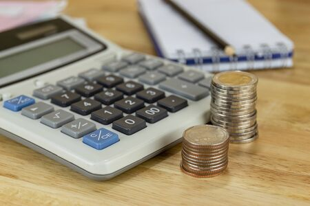 the stack of coin with calculator on wood table at office, concept of calculating expenses, incomes and expenses. Archivio Fotografico