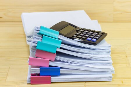 pile of papers with Calculator at work office for business on the table, concept document in work office