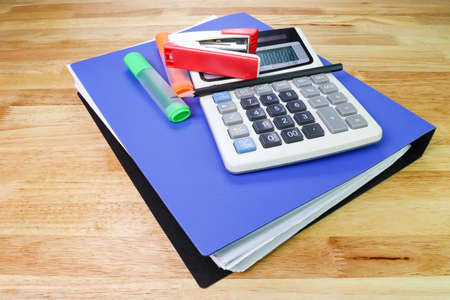 blue file folder calculator pencil with Color highlight and Stack paper file for office work on wood table
