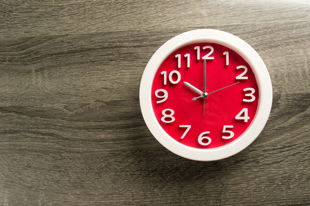 Red clock on wood background .Make on color background concept