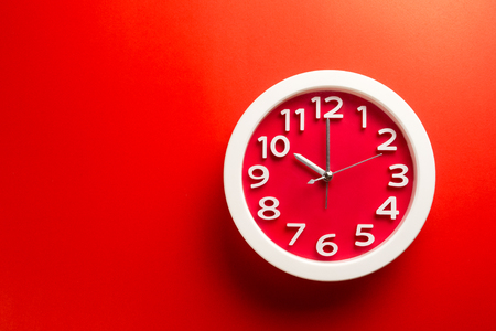 Red clock on red background .Make on color background concept.