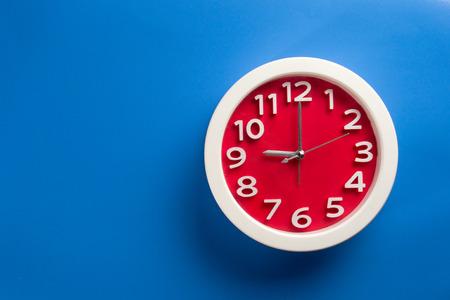 Red clock on blue background .Make on color background concept Standard-Bild