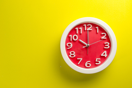 Red clock on yellow background .Make on color background concept Standard-Bild