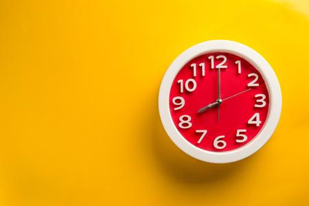 Orologio rosso su sfondo giallo. Fare sul concetto di sfondo di colore